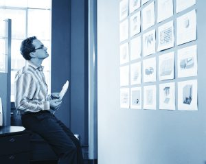 Businessman looking at charts hanging on wall, side view